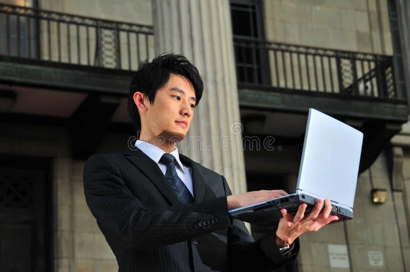 Computer-ausgebufftes asiatisches Leitprogramm, das ein Notizbuch verwendet lizenzfreie stockfotografie