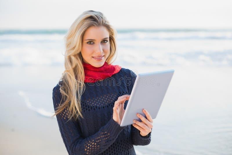 Computer biondo sexy allegro della compressa della tenuta fotografie stock libere da diritti