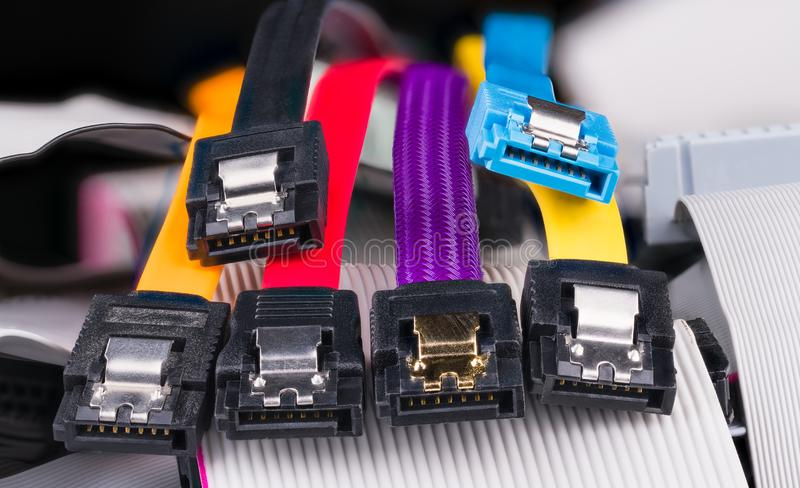 Internal serial connectors with colorful flat cables on pile of obsolete parallel cords. Computer bus interface for storage devices as hard, optical or solid stock images