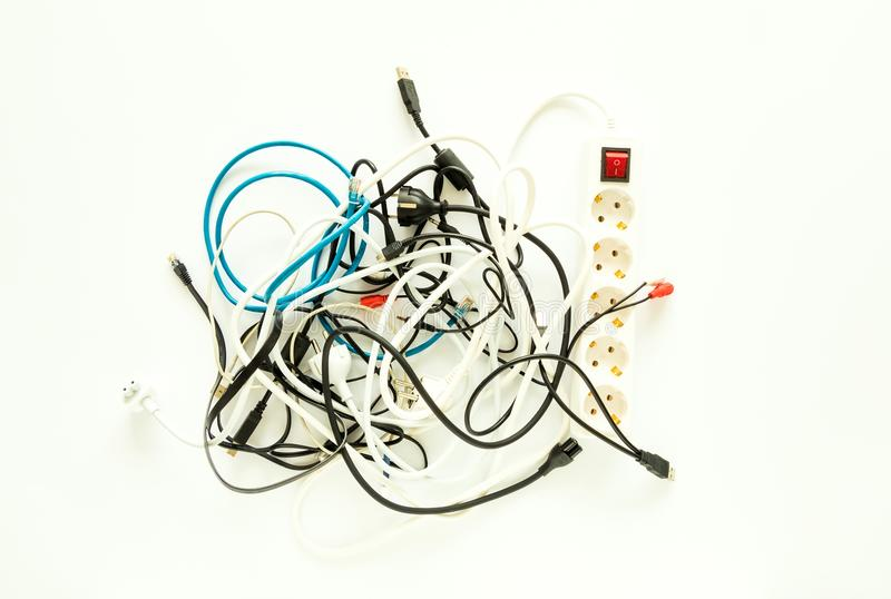 Computer cables, wires, chargers in a messy heap. Home electronic chaos concept, flat lay stock photos