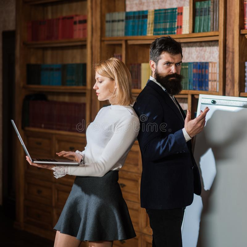 Computer concept. Woman and man develop new project using computer. University students surfing Internet in laptop royalty free stock images