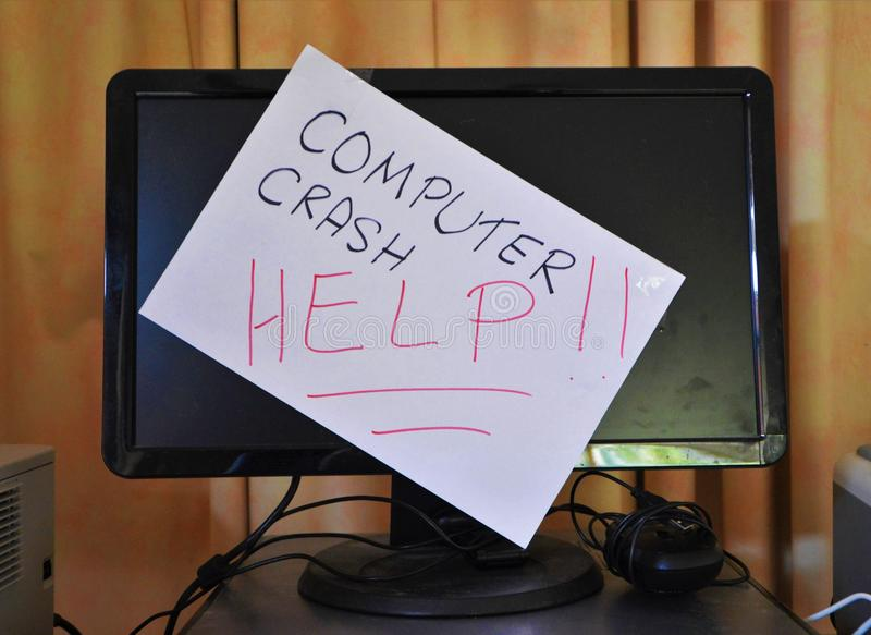 Computer crash. Handwritten message on white paper in black and red marker states 'Computer Crash - Help!' The message is attached to the monitor of a desktop royalty free stock photos