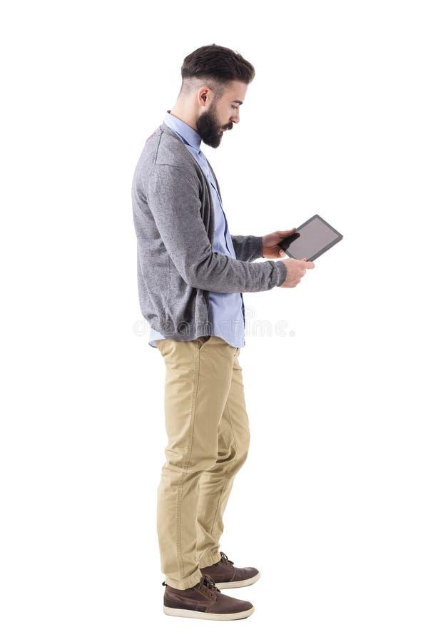 Computer del cuscinetto dei pantaloni a vita bassa dell'uomo d'affari della compressa alla moda della tenuta e di sorveglianza Vi fotografia stock libera da diritti