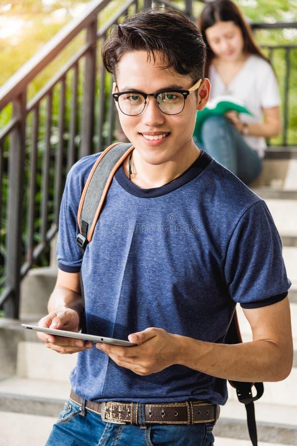 Computer della compressa della tenuta del supporto dello studente maschio del ritratto immagini stock
