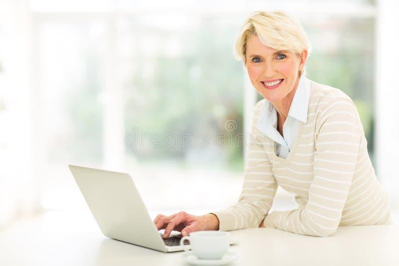 Computer della donna invecchiato mezzo fotografia stock