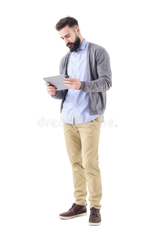 Computer della giovane dell'uomo d'affari compressa casuale astuta adulta della tenuta e di sorveglianza fotografia stock