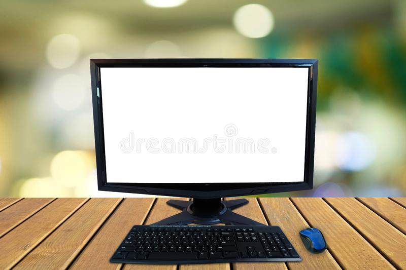 Computer desktop pc with blank screen and keyboard and wireless mouse on wooden floors with blurred colorful bokeh stock images