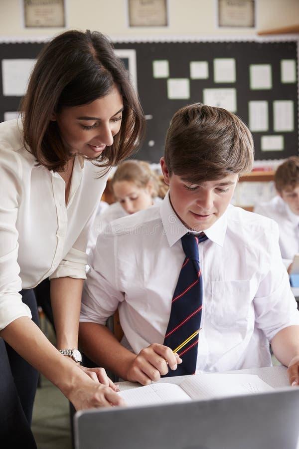 Computer di Helping Pupil Using dell'insegnante femminile in aula immagini stock libere da diritti