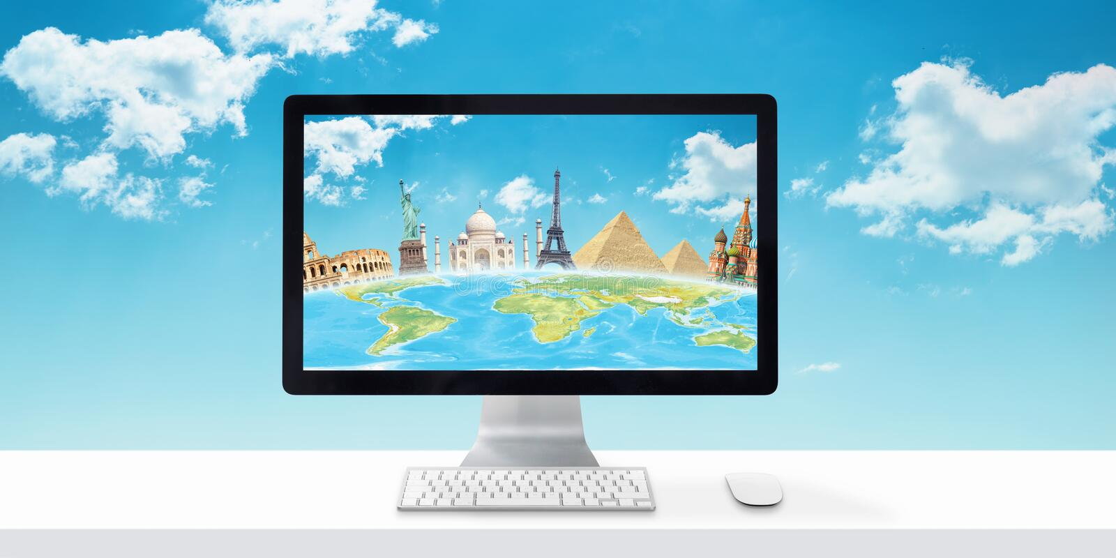 Computer display with globe and famous world sights on white desk royalty free stock photo