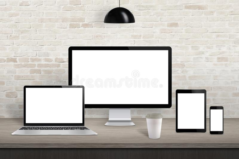 Computer display, laptop, tablet and mobile phone with screen on office desk. White screen for web site design promotion. Brick wall in background stock photos