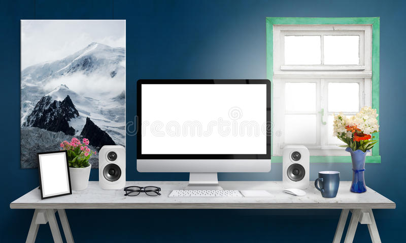 Computer display on office desk. , white screen for mockup. Creative modern desk with speakers, picture frame, glasses, keyboard, mouse, flowers, cup of coffee royalty free stock images
