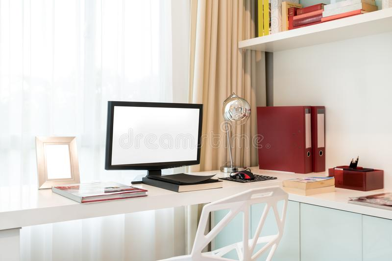 Computer display and office tools on desk in home. Desktop computer screen isolated. Modern creative workspace background. stock photo
