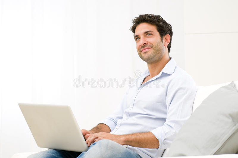 Computer dreams. Smiling dreaming young man looking up while working at laptop computer