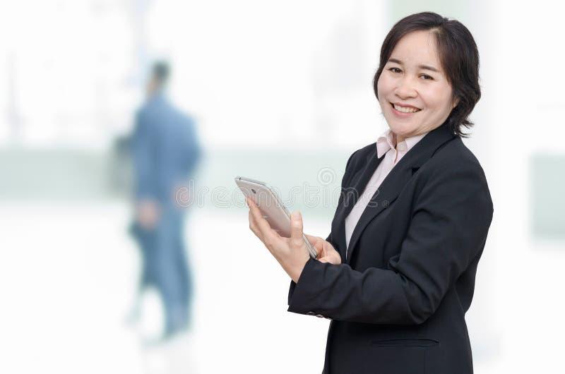 Computer e sorrisi della compressa della tenuta della donna di affari fotografia stock libera da diritti