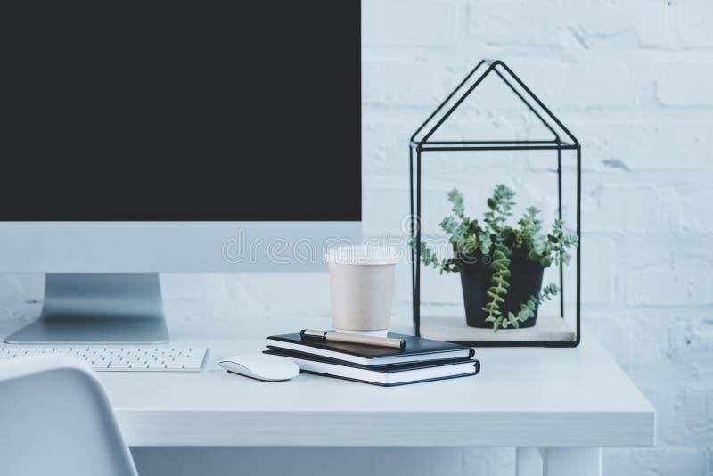 computer e tazza di caffè eliminabile sulla tavola in posto di lavoro moderno fotografie stock libere da diritti