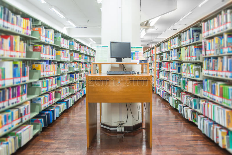 Computer in een bibliotheek met vele boeken en planken royalty-vrije stock afbeelding