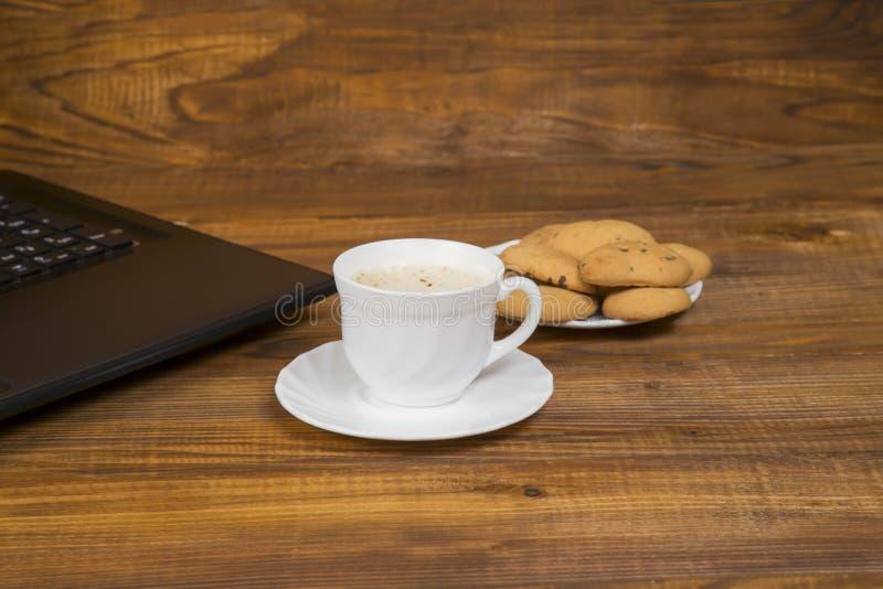 Computer een kop koffie en koekjes stock fotografie