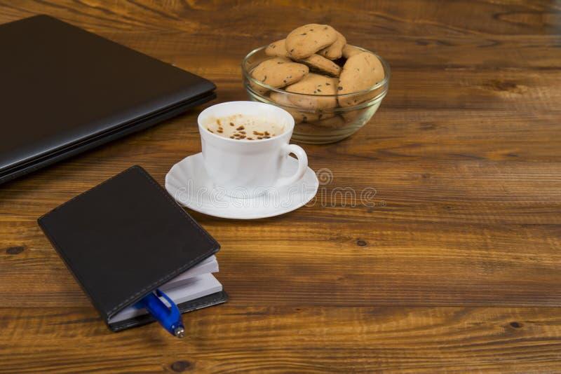 Computer een kop koffie en koekjes stock foto's