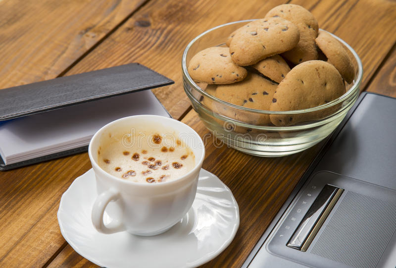 Computer een kop koffie en koekjes stock afbeelding