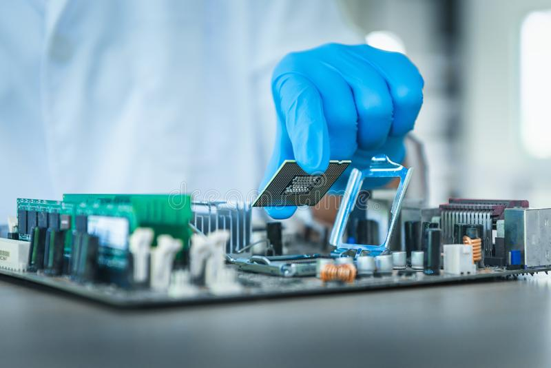 Computer engineer assembly microprocessor CPU into electronic motherboard., Close-up of technician putting microchip to circuit stock photography