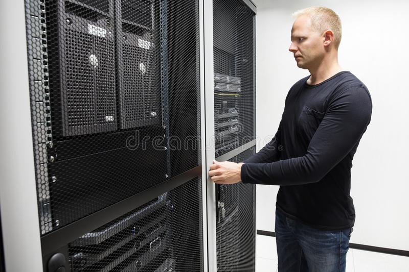 Computer Engineer Opening Server Rack Door In Data Center stock images