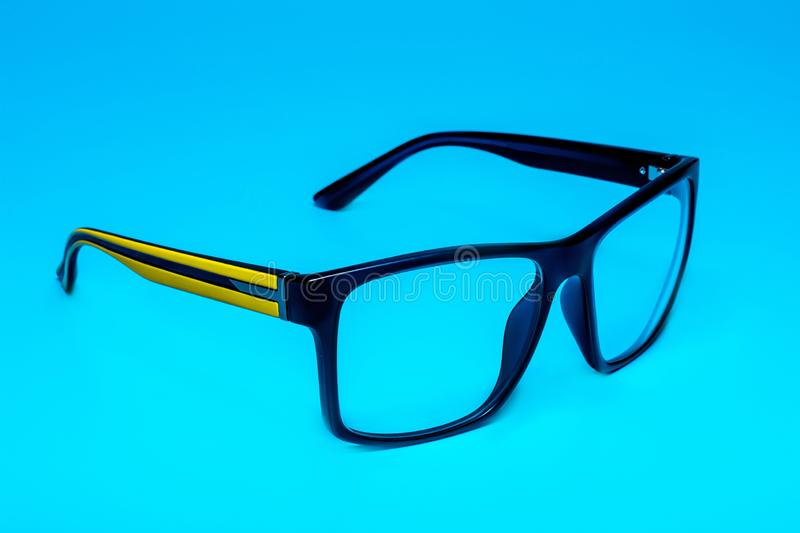 Computer eye protection glasses with a yellow shackle close up on a blue background, isolation royalty free stock image