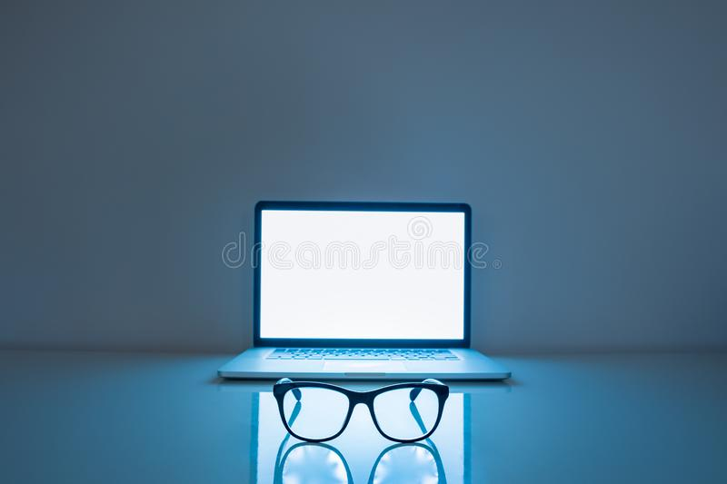 Computer eyeglasses in front of a laptop, low-key image. royalty free stock photo