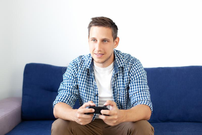 Computer games competition. Game concept. Gamer guy plays a video game with a joystick at home. A man in a shirt sitting on a sofa. Plays a video game with a stock images