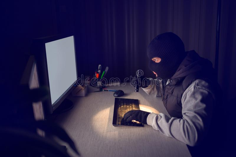 Computer hacker stealing data information off a computer. Computer hacker in a balaclava working in the darkness stealing data and personal identity information stock image