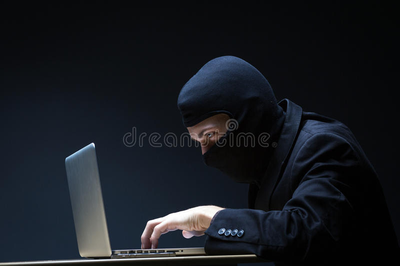 Computer hacker. In a balaclava working in the darkness stealing data and personal identity information off a laptop computer stock photo