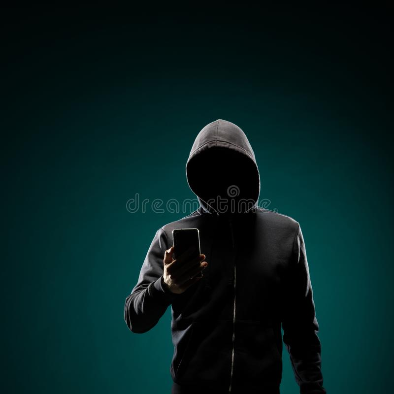 Computer hacker in hoodie. Obscured dark face. Data thief, internet fraud, darknet and cyber security concept. Portrait of computer hacker in hoodie. Obscured royalty free stock photography