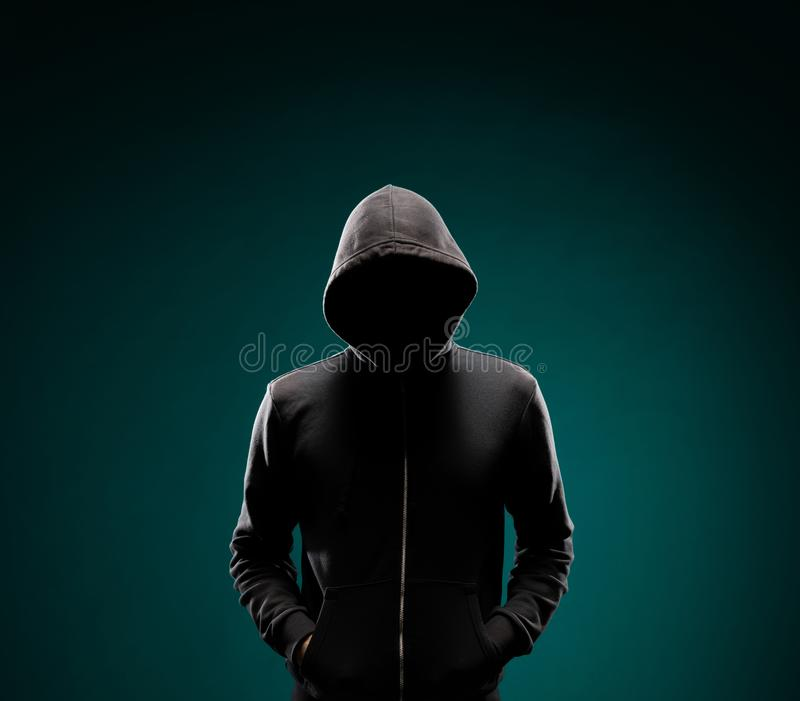 Computer hacker in hoodie. Obscured dark face. Data thief, internet fraud, darknet and cyber security concept. royalty free stock photography