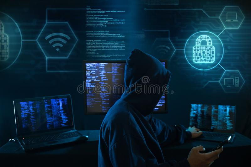 Computer hacker - Internet crime concept with digital interface around. Internet crime concept. Hacker working on a code on dark digital background with digital stock photo