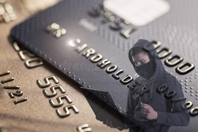 Computer hacker with laptop against background with credit cards. Network and banking security concept royalty free stock image