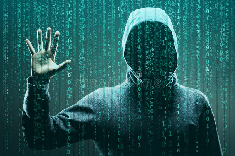 Computer hacker in mask and hoodie over abstract binary background. Obscured dark face. Data thief, internet fraud. Darknet and cyber security concept stock photo