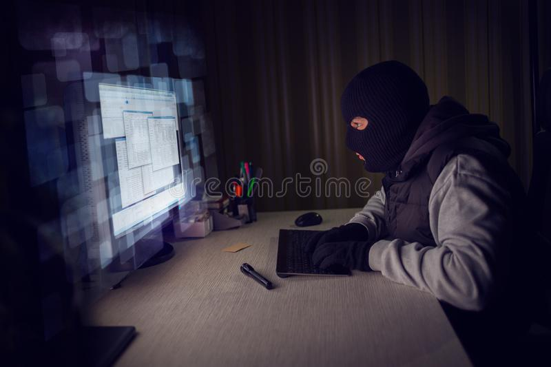 Computer hacker stealing data from a computer. Concept for network security, identity theft and computer crime stock image
