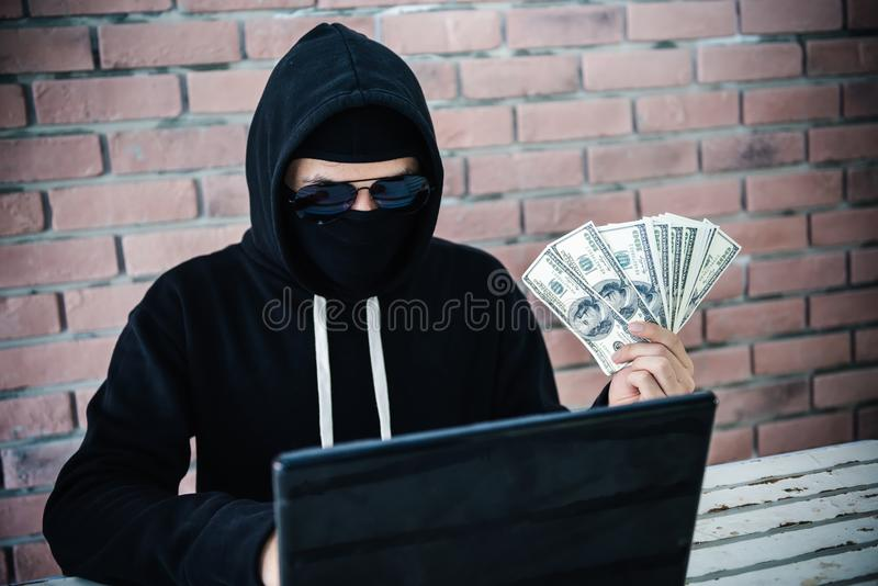 Computer hacker trying to accessing information privacy of the c. Ompanies and showing money income from robberies royalty free stock photo