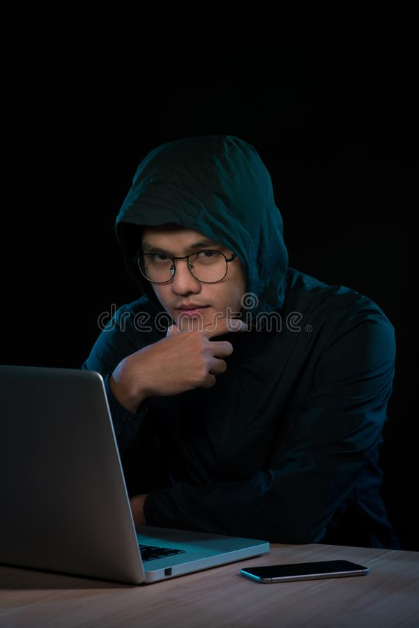 Computer hacker working in dark room.  stock image