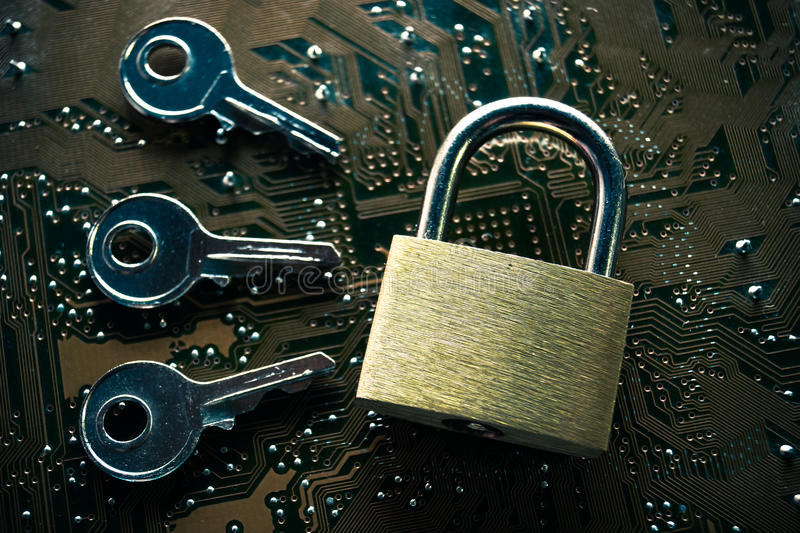 Computer hacking. A security lock on a computer circuit board surrounded by keys / random password hacking concept stock images