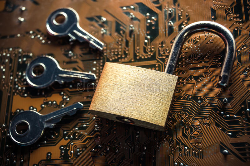 Computer hacking. Unlock security lock on a computer circuit board surrounded by keys / random password hacking concept royalty free stock photo