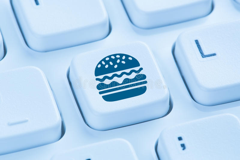 Computer hamburger cheeseburger fast food ordering online order. Delivery symbol blue keyboard royalty free stock photos