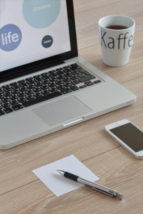 Computer, Handy, Tasse Kaffee mit Buchstaben, Stift und Papier für Anmerkungen lizenzfreie stockfotos