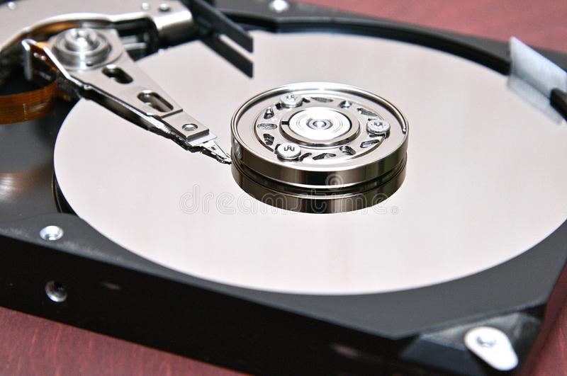 Computer hard disk-hard drive on an isolated background. Internal parts of a hard disk on an isolated braun,wood background stock images