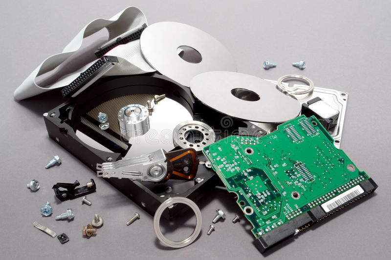 Computer Hard Drive Crashed and Broken Apart. Crashed and broken apart dismantled computer hard drive with scattered component parts showing loose disks and stock image