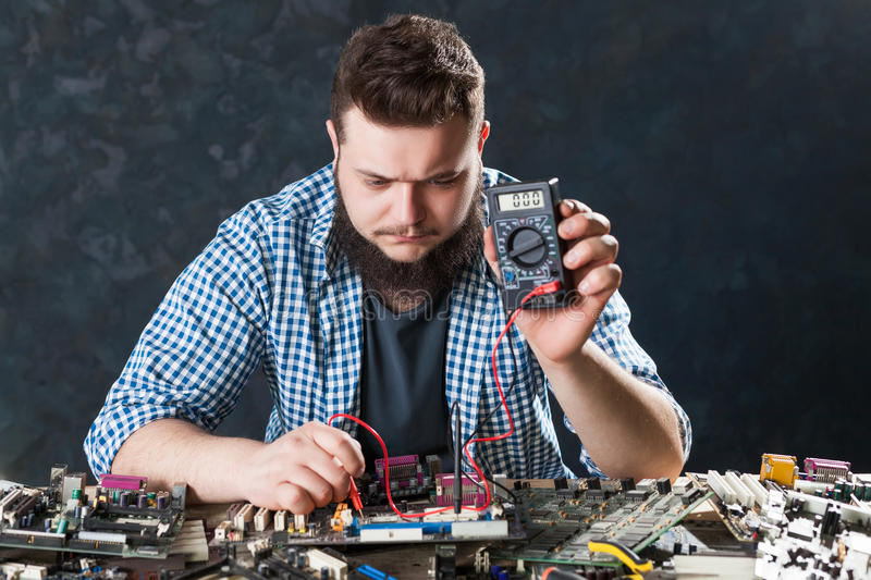 Computer hardware electronic components diagnostic. Computer hardware or electronic components diagnostic. Male engineer hads fixing problem with pc motherboard royalty free stock photography