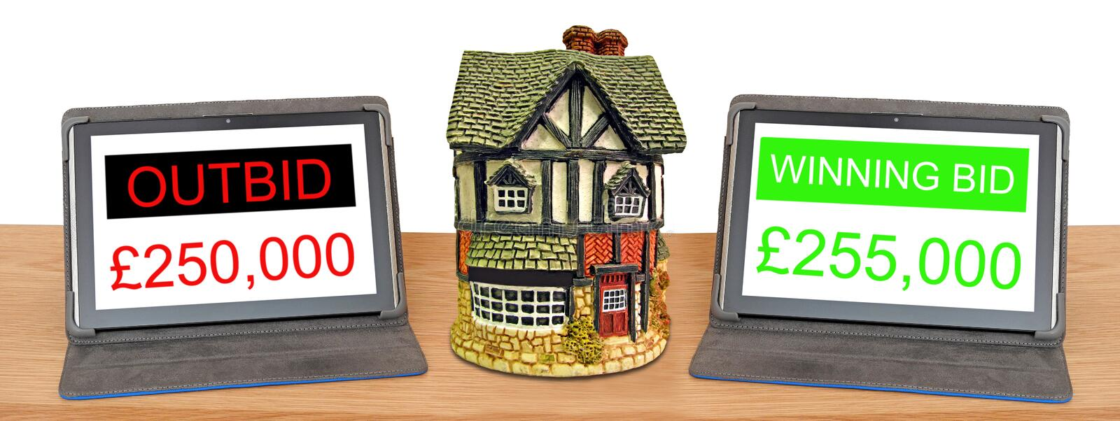 Computer internet online property auction bidding. Concept photo of internet online auction property sales bidding showing two tablets bidding for property home stock image