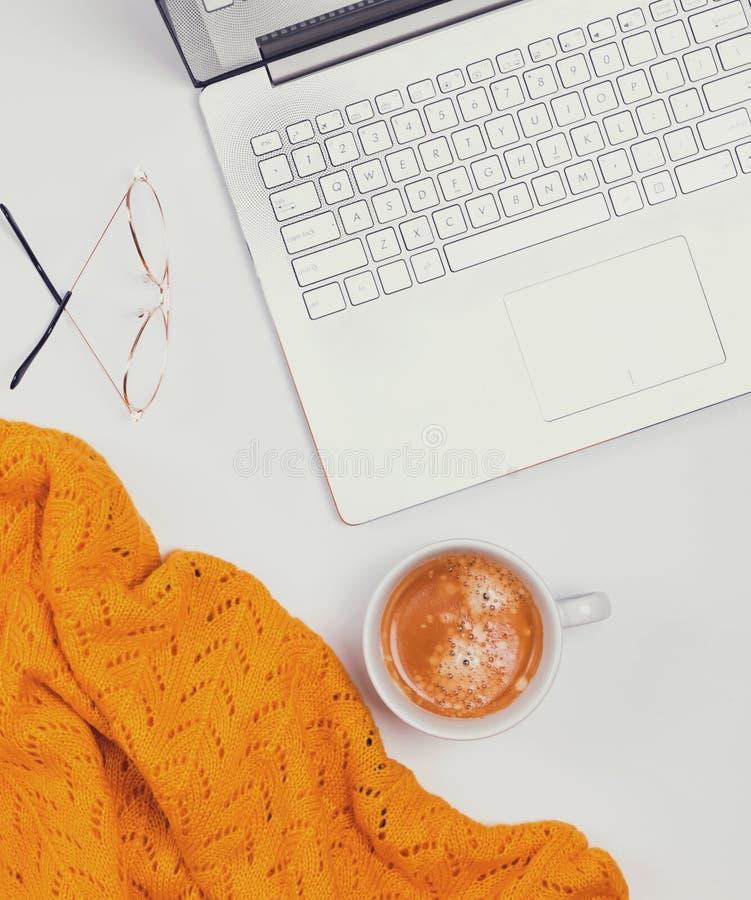 Computer, Kaffee und gelbe Strickjacke auf dem weißen Hintergrund lizenzfreie stockfotos