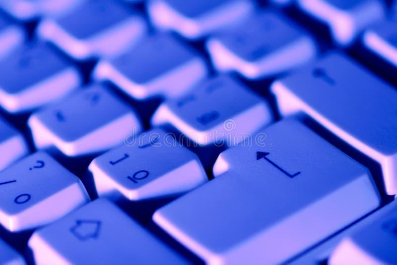 Computer keyboard. Under blue light stock photography