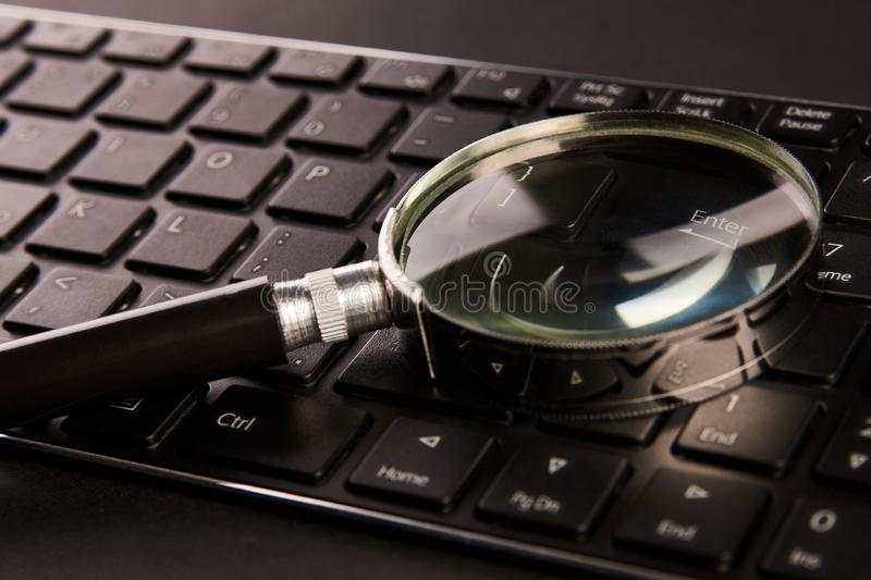 Computer keyboard and magnifying glass, close-up. Computer security concept stock image