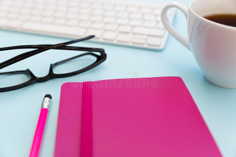 Computer keyboard pink notebook pencil coffee and eyeglesses stock image
